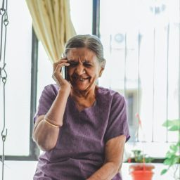 older woman on a cell phone while looking very happy