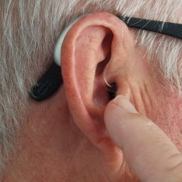 Man points at hearing aid