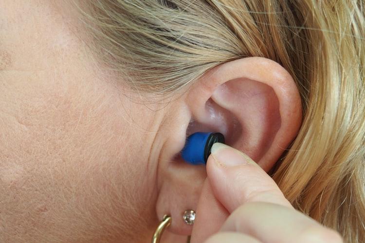 Woman places earplug in her ear.