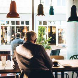 An older man sitting inside a coffee shop.