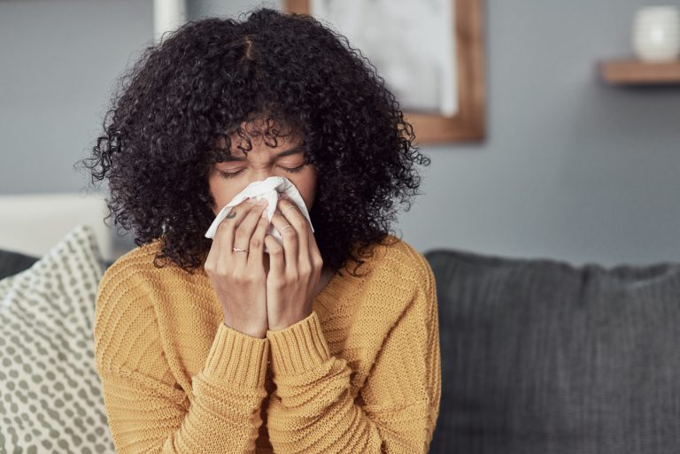Woman with a cold sneezing